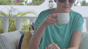 Beautiful young woman drinking coffee at garden villa. stock footage