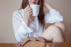 Beautiful young woman drinking coffee Stock Images
