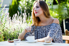 Beautiful young woman drinking coffee in the home garden. Royalty Free Stock Photo