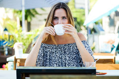 Beautiful young woman drinking coffee in the home garden. Royalty Free Stock Image