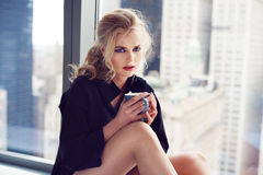 Beautiful young woman drinking coffee at home at the morning sitting by the window Royalty Free Stock Photos