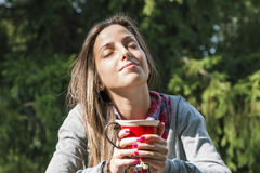 Beautiful young woman drinking coffee in a morning park Stock Photos