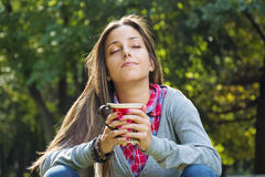 Beautiful young woman drinking coffee in a morning park Royalty Free Stock Image