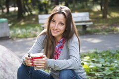 Beautiful young woman drinking coffee in a morning park Stock Photography
