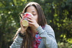 Beautiful young woman drinking coffee in a morning park Royalty Free Stock Photos