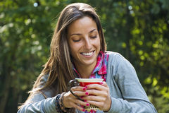Beautiful young woman drinking coffee in a morning park Stock Image