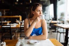 Woman drinking coffee in restaurant. Beautiful young woman drinking coffee in restaurant Stock Image