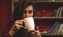 Beautiful Young Woman Drinking Coffee or Tea. Beauty Model Girl enjoying beverage. Lady holding Cup of coffee or tea stock photo