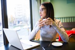 Beautiful young woman drinking coffee while using her laptop in the coffee shop. Royalty Free Stock Images