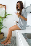 Beautiful young woman drinking coffee and using her mobile phone Royalty Free Stock Images