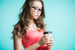 Beautiful young woman drinking coffee. Young brunette woman holding a paper Cup on her hand on a blue background royalty free stock photography