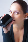 Beautiful young woman drinking from a cup Stock Image