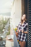 Beautiful young woman is drinking cup of coffee or tea while standing on the balcony. Dressed only in one paid shirt. Sun light flair effect Stock Images