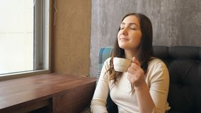 Beautiful young woman drinking with cup of hot coffee near window at cafe stock footage