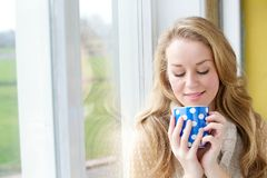 Beautiful young woman drinking a cup of tea. Close up portrait of a beautiful young woman drinking a cup of tea by a window at home Royalty Free Stock Photography