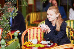 Beautiful young woman drinking hot chocolate in Parisian outdoor cafe Stock Image