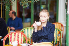 Beautiful young woman drinking hot chocolate in Parisian outdoor cafe Stock Images