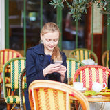 Beautiful young woman drinking hot chocolate in Parisian outdoor cafe Royalty Free Stock Image