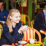 Beautiful young woman drinking hot chocolate in Parisian outdoor cafe Royalty Free Stock Images