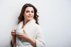 Beautiful young woman is drinking hot coffee stock photo