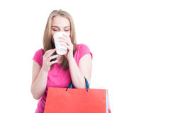Beautiful young woman drinking hot coffee and relaxing on shopping Stock Photos
