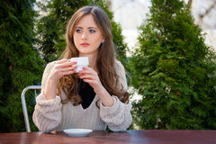Beautiful young woman drinking hot coffee or tea in the morning at restaurant. Lifestyle photo, girl enjoying her morning coffee i Royalty Free Stock Images