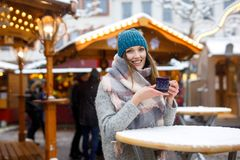 Beautiful young woman drinking hot punch, mulled wine on German Christmas market. Happy girl in winter clothes with royalty free stock image