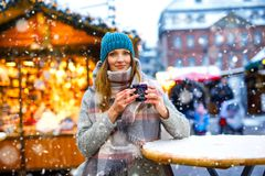 Beautiful young woman drinking hot punch, mulled wine on German Christmas market. Happy girl in winter clothes with royalty free stock photography