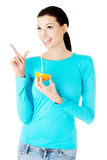 Beautiful young woman drinking juice from orange. Royalty Free Stock Images