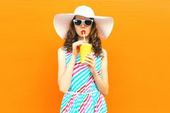 Beautiful young woman drinking juice in summer straw hat, colorful striped dress on orange wall royalty free stock image