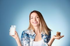 Beautiful young woman drinking milk. With cookies on color background Royalty Free Stock Photo