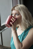 Beautiful Young Woman Drinking from Red Coffee Cup Stock Photography