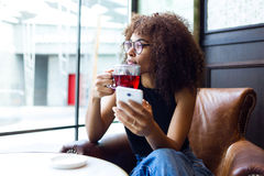 Beautiful young woman drinking red tea in a coffee shop. Royalty Free Stock Photos
