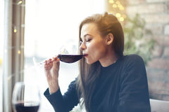 Beautiful young woman drinking red wine with friends in cafe, portrait with wine glass near window. Vocation holidays evening conc. Ept royalty free stock photo