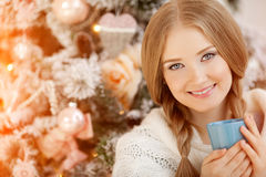 Beautiful young woman drinking tea at the Christmas tree. Beauti. Ful girl celebrates Christmas with cup of cocoa Stock Photo