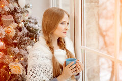 Beautiful young woman drinking tea at the Christmas tree. Beautiful girl celebrates Christmas with cup of cocoa. royalty free stock image