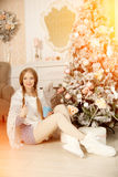 Beautiful young woman drinking tea at the Christmas tree. Beauti Stock Photography