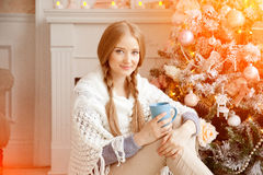 Beautiful young woman drinking tea at the Christmas tree. Beauti. Ful girl celebrates Christmas with a cup of cocoa Royalty Free Stock Images