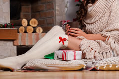Beautiful young woman drinking tea. Close-up of young woman legs drinking tea at the Christmas tree over living room Royalty Free Stock Photos