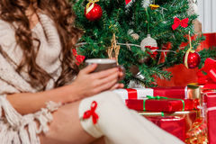 Beautiful young woman drinking tea. Close-up of young woman legs drinking tea at the Christmas tree over living room Stock Photos