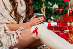 Beautiful young woman drinking tea. Close-up of young woman legs drinking tea at the Christmas tree over living room Royalty Free Stock Photo