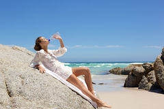 Beautiful young woman drinking water at the beach Stock Photos