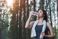 Beautiful young woman drinking water bottle after exercise fitne Stock Photos