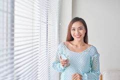 Beautiful young woman drinking water at home stock photo