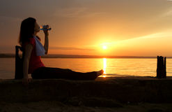 Beautiful young woman drinking water - sunset. Royalty Free Stock Image