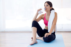 Beautiful young woman drinking water after a workout at home. Stock Images