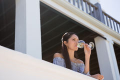 Beautiful young woman drinking white wine in balcony at restaurant Stock Images