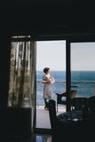 Beautiful young woman drinking wine on a balcony with beautiful ocean view Royalty Free Stock Photos