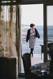 Beautiful young woman drinking wine on a balcony with beautiful ocean view Royalty Free Stock Photography