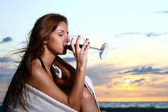 Beautiful young woman drinking wine on beach Stock Photos